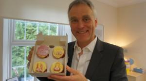 Consultant plastic surgeon Mr Adrian Richards holding cupcakes